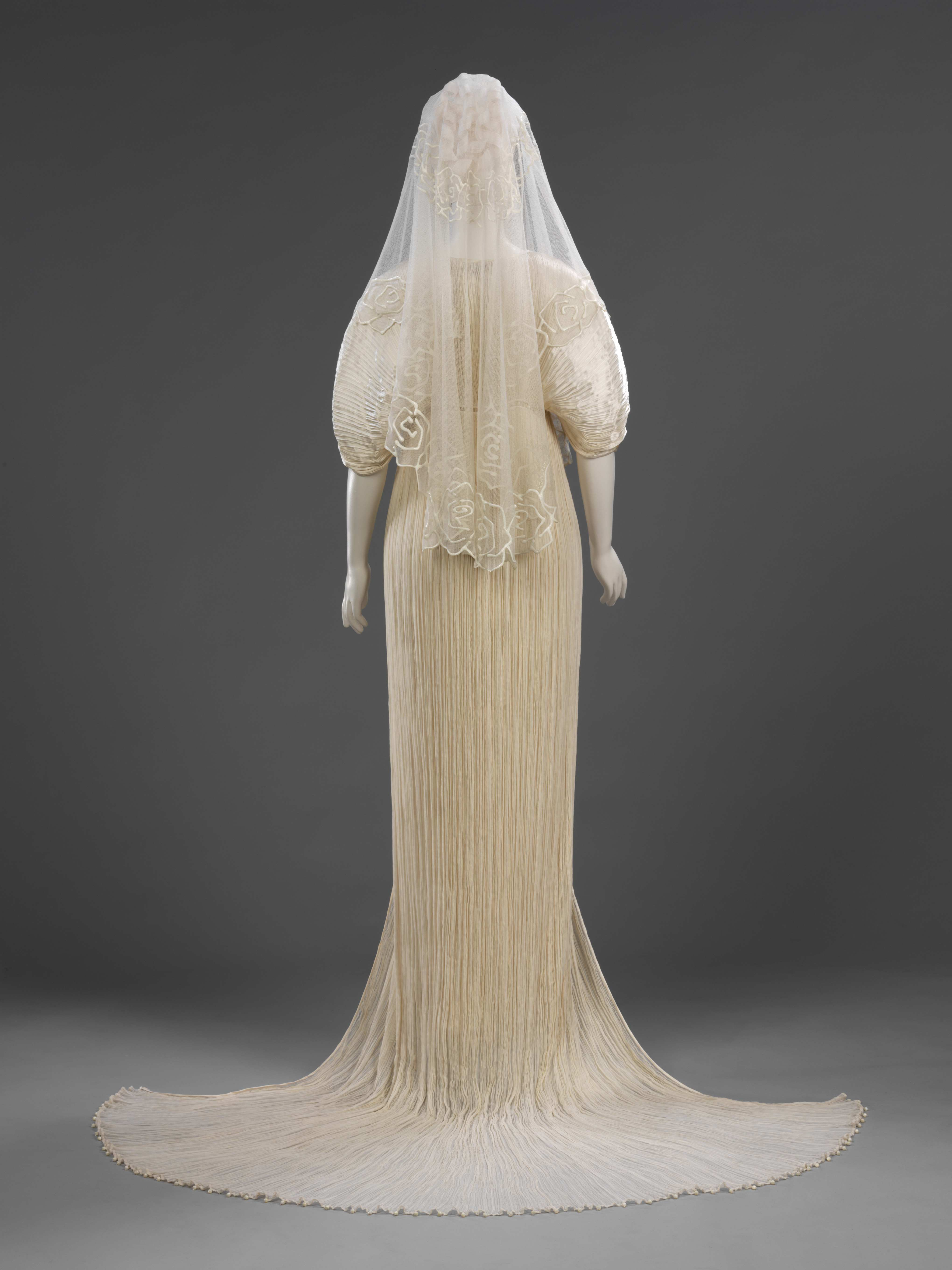 Pleated silk wedding dress and coat, net veil decorated with silicone rubber, by Ian and Marcel, London, 1989. Bequeathed by Ian and Marcel
