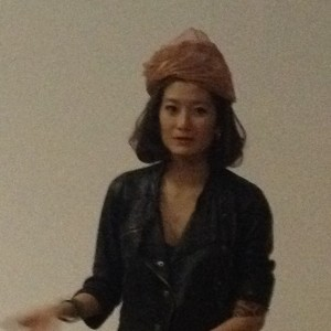Elaine Yan Ling Ng mid-presentation, In her interview with Kim Hill she elaborates on her head-dress which is fashioned from copper, nylon and silk.